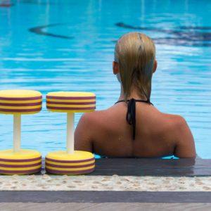 Chica de espaldas en piscina al lado de dos pesas